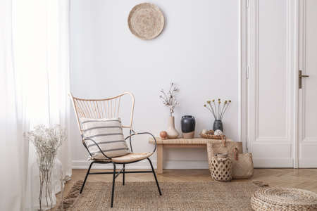 Flowers on wooden stool next to armchair in white loft interior with pouf and plate. Real photo