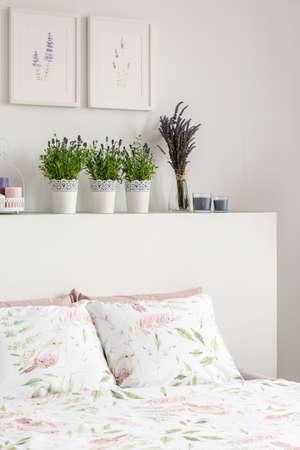 Flores de lavanda en el cabecero de la cama con almohadas en el interior del dormitorio blanco con carteles. Foto real