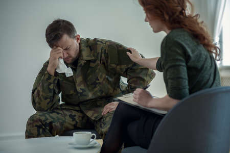 Professional psychiatrist supporting crying soldier with war syndrome in the office