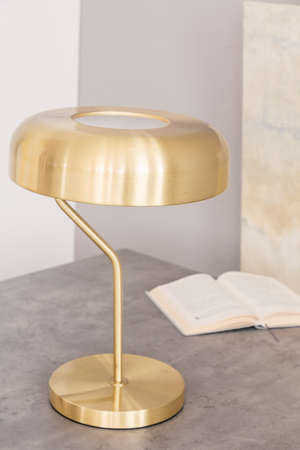 Close-up of a minimal stylish gold color desk lamp and an open book on a table in an office interior. Real photo.
