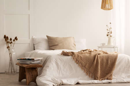 Blanket on white bed in natural bedroom interior with plants and wooden stool. Real photo