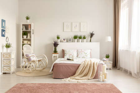 Rocking chair next to bed with blanket in spacious white bedroom interior with pink carpet. Real photo Standard-Bild - 108810598