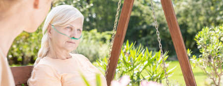 Panorama of sick elderly woman during treatment in hospitals garden Stock Photo
