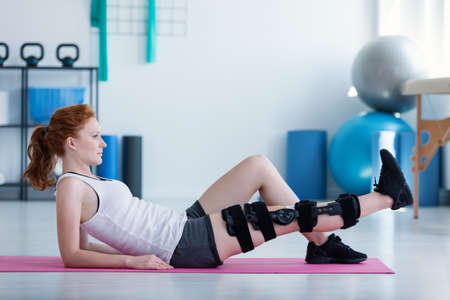 Sportlerin auf der Matte macht Übungen mit gebrochenem Bein während der Rehabilitation