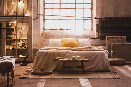 Lights on shelves next to bed with sheets and pillows in bright bedroom interior with window. Real photo