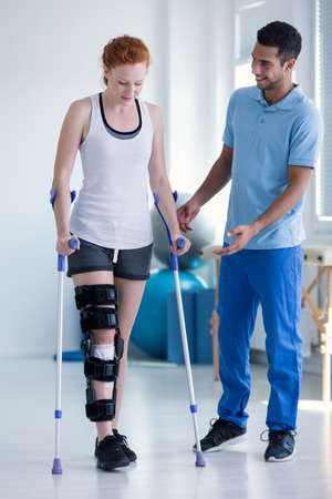 Physiotherapist helping woman with stiffener on the leg walking with crutches