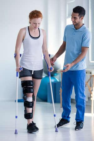 Physiotherapeutin hilft Frau mit Versteifung am Bein beim Gehen mit Krücken Standard-Bild