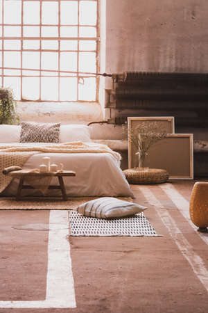 Pillow on the floor in bright bedroom interior with cushions on bed next to window and plant. Real photo