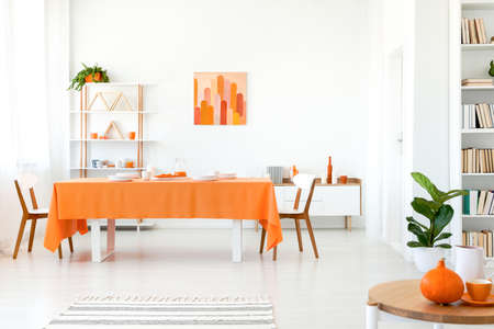 White dining room with orange details such as tablecloth, coffee mugs and painting Real photo concept