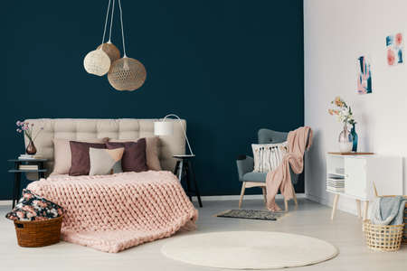 Grey armchair with powder pink blanket and cushion standing in the corner of white and blue bedroom interior with king-size bed with handmade coverlet and many pillows Foto de archivo - 108810663