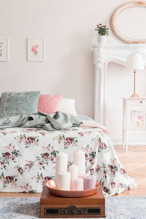 English style bedroom interior with a bed dressed in rose pattern bedding and green, pink and white cushions. Candles on the floor in front of the bed. Real photo. Banque d'images