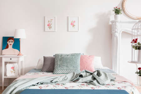 Pastel bedroom interior with roses as a pattern on bed linen and illustrations on the wall. Self portrait of a woman on a nightstand. Real photo. Stok Fotoğraf