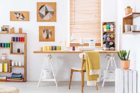 Echte foto van een kleurrijk kamerinterieur met een bureau, naaimachine en draden Stockfoto