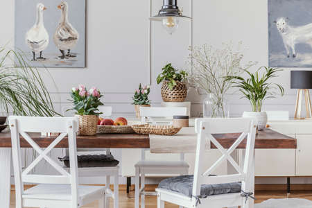 White dining room interior with posters and chairs at wooden table with flowers. Real photo Foto de archivo - 108810699