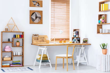 Real photo of a creative room interior with a desk, shelf and knitting wool Stok Fotoğraf