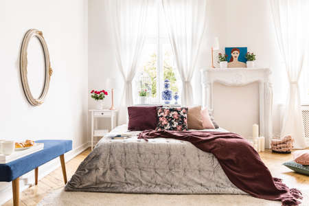 Woman's bedroom interior with vintage accents. A bed dressed in a silver throw, a brown blanket and many pillows against a wall with an ornamented fireplace portal and a sunny window. Real photo Stock Photo - 108810703