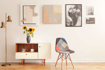 Colorful chair standing in white living room interior with gallery on wall, cupboard with flowers and tea cups in real photo