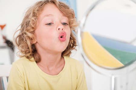 正しい発音の授業中に鏡の前で話すことを学ぶ子供