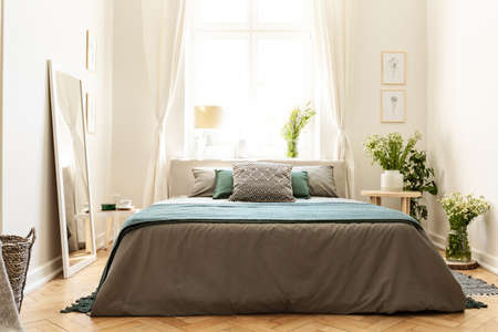 Beige, green and gray bedroom interior in a tenement house with a bed against a sunny window and bunches of wild flowers. Real photo.