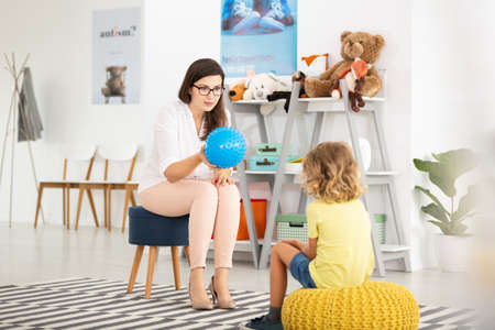 Teacher with blue ball and kind kid in the classroom with toys