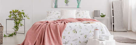 Real photo of a romantic bedroom interior with a pink blanket on a double bed with floral sheets