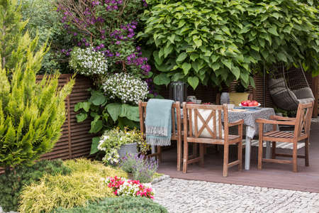 Beautiful backyard with a terrace and garden furniture. Real photo Imagens