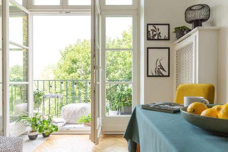 Immeuble avec un balcon décoré de plantes. Gros plan de fruits sur une table
