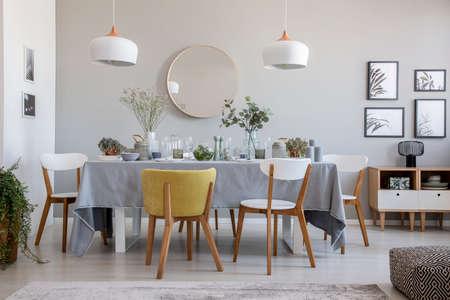 Echte foto van een elegant eetkamerinterieur met een gedekte tafel, stoelen, spiegel aan de muur en lampen