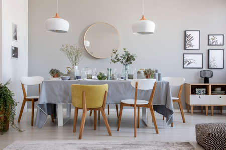 Foto real de un elegante comedor interior con una mesa puesta, sillas, espejo en una pared y lámparas.