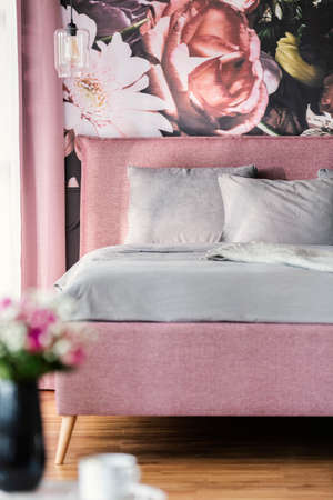 Grey pillows and sheets on pink bed with flower wallpaper in feminine bedroom interior. Real photo