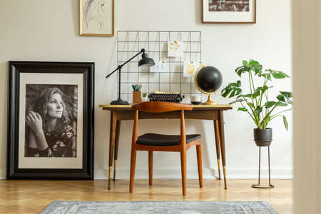 Wooden chair at desk with lamp in white freelancers interior with plant and posters. Real photo 版權商用圖片