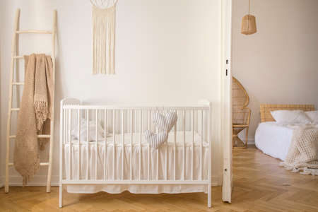 Wooden crib with cushions standing in real photo of white kid room interior with blanket on ladder and macrame on the wall Фото со стока