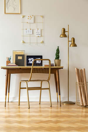 Gold chair at desk with laptop in white home office interior with lamp and poster. Real photo