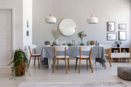 Grey dining room interior with a table, chairs and plant. Idea for a dinner