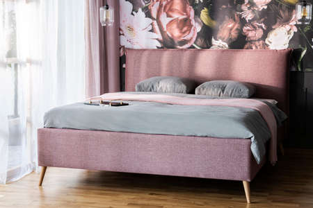 Pink blanket and grey cushions on bed in bright bedroom interior with flower print on the wall. Real photo