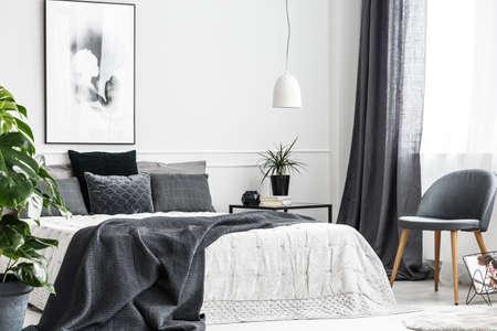 Nowoczesne, szare krzesło z drewnianymi nogami przy oknie jasnego wnętrza sypialni z ciemnoszarym kocem na wygodnym łóżku Zdjęcie Seryjne