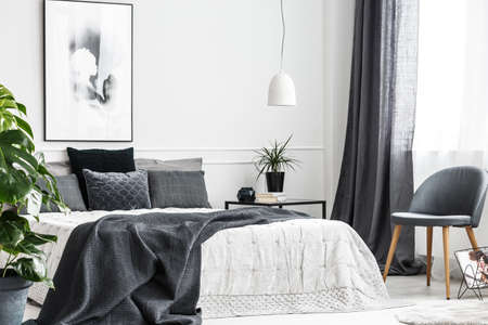 Silla moderna y gris con patas de madera junto a una ventana del interior de un dormitorio luminoso con una manta gris oscuro en una cama cómoda Foto de archivo