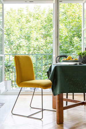 Yellow chair next to a table in a dining room interior with a terrace in the background