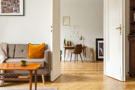 Holztisch vor Sofa und Plakaten im Innenraum der weißen Wohnung mit Stuhl am Schreibtisch. Echtes Foto