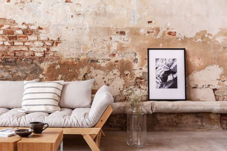 Poster and flowers next to grey wooden couch with pillows in flat interior with brick wall. Real photo