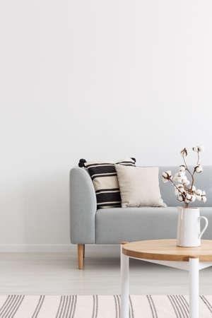 Flowers on wooden table in white minimal flat interior with pillows on grey sofa near rug. Real photo