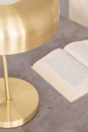 Top view and close-up of a gold color lamp standing next to an open book on a gray marble top of a desk in an office interior. Blurred view of the book. Real photo.