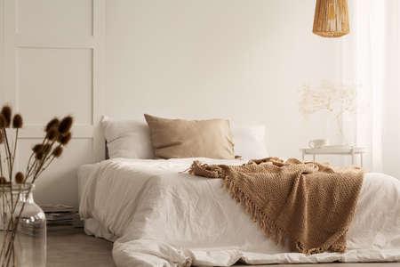 Blumen und Lampe im weißen natürlichen Schlafzimmerinnenraum mit Decke und Kissen auf Bett. Echtes Foto Standard-Bild
