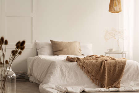 Flowers and lamp in white natural bedroom interior with blanket and pillows on bed. Real photo Фото со стока