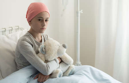 Triste niña enferma con pañuelo rosa abrazando peluche en el hospital Foto de archivo