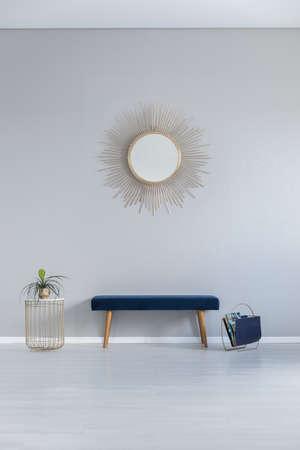 Gouden spiegel aan de muur boven de blauwe bank in grijze minimale hal winteri en tafel. Echte foto Stockfoto