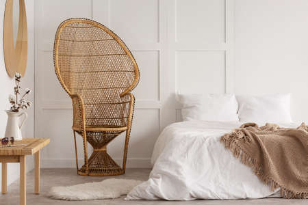 Flowers on wooden table next to rattan chair in white bedroom interior with blanket on bed. Real photo