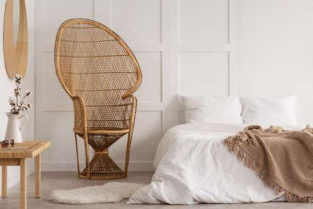 Fleurs sur table en bois à côté de chaise en rotin dans l'intérieur de la chambre blanche avec couverture sur le lit. Vrai photo Banque d'images