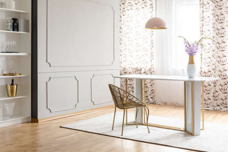 Real photo of a glamour dining room interior with a table, chair, flower and empty wall. Place your painting