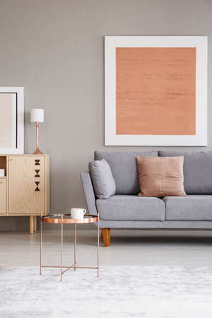 Real photo of a copper table in a living room interior with a modern painting on a wall and sofa